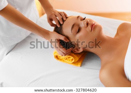 Face massage. Close up portrait of young woman during facial massage with rejuvenating, refreshing, regenerative, anti-aging cream in  beauty cosmetology esthetics medical spa salon or clinic. - stock photo