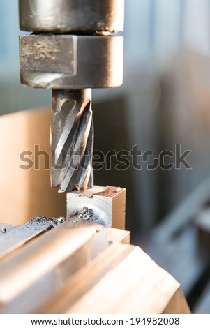 Face milling cutter in chuck during milling iron piece at industrial manufacture factory workshop - stock photo