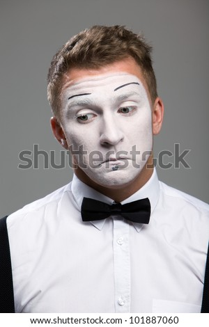 Face mime close-up emotions of confusion, black bow tie, theatrical makeup, isolated on a gray background - stock photo