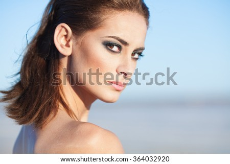 Face of a beautiful brunette woman with smoky eyes makeup - stock photo