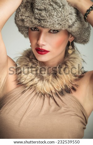 face of a beautiful woman with fur collar and hat holding hands on her head