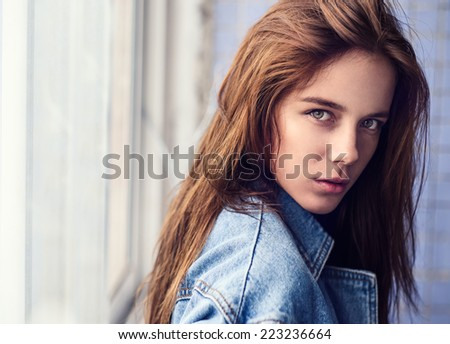 face of a beautiful young girl with a sexy look in a denim jacket at home - stock photo