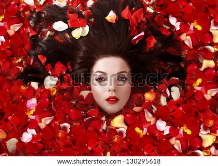Face of a beautiful young woman in rose petals, representing the concept of beauty. - stock photo