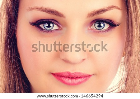 Face of a beautiful young woman with blue eyes. Closeup  - stock photo