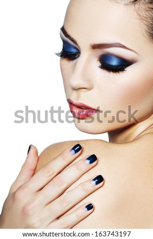 Face of a beautiful young woman with brightly blue make-up. Isolated on white
