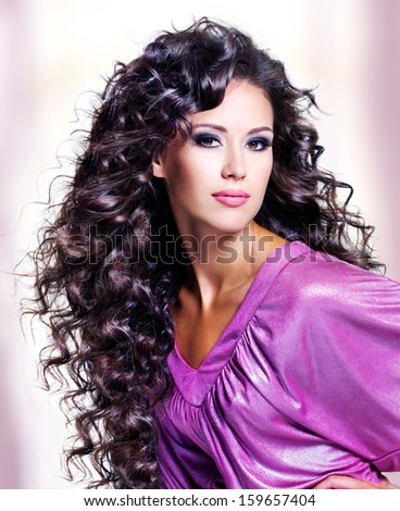 Face of  a beautiful young woman with brown long ringlets hairs and fashion makeup