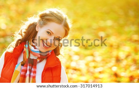 face of a happy girl with autumn leaves on a walk