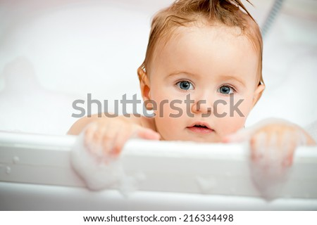 face of a little baby in the bathroom - stock photo