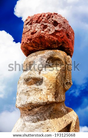 Face of a maoi with a red hat in Easter Island against bright sky - stock photo