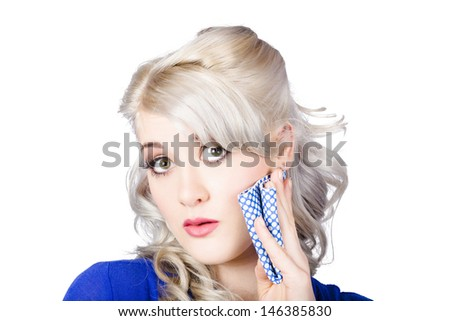 Face of a shocked pinup woman holding cleaning rag to cheek, isolated over white background