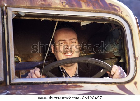 Face of a smiling man through a broken windshield of a very old truck
