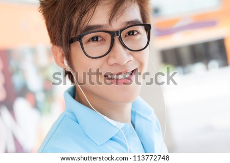 Face of a teenager in glasses smiling at camera - stock photo