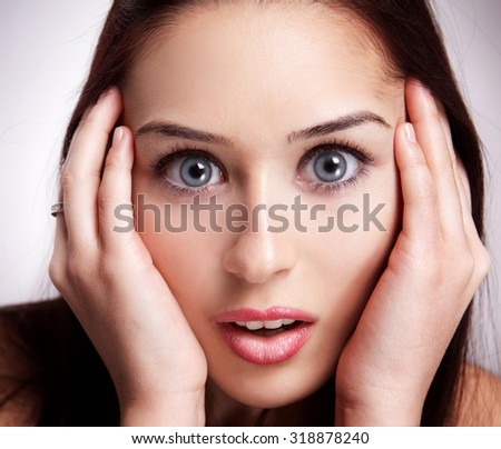 Face of amazed and surprised young woman - stock photo