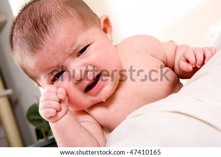 Face of an unhappy unisex Caucasian Hispanic baby crying with tears while rubbing eye.