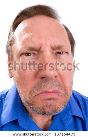 Face of angry senior adult man with Parkinson's disease as he stares with a threatening look.