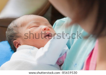 Face of Asian female newborn fall asleep in mother's arms - stock photo