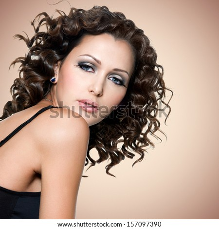 Face of  beautiful adult woman with curly hairs over brown background - stock photo