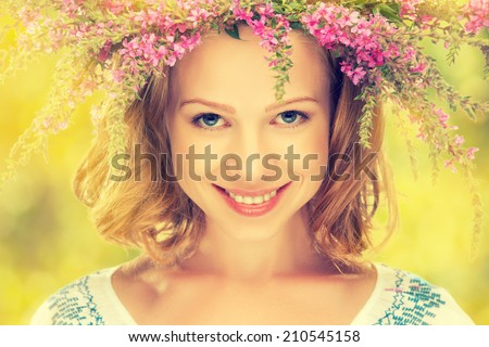 face of beautiful happy Slavic girl in a wreath of summer flowers on nature - stock photo