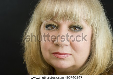 face of beautiful middle-aged blond woman on black - stock photo