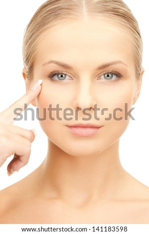 face of beautiful woman pointing at her eye area - stock photo