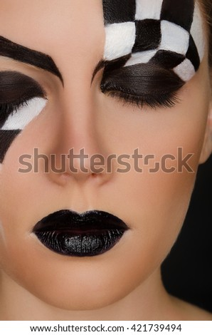face of beautiful woman with black and white pattern on black background - stock photo