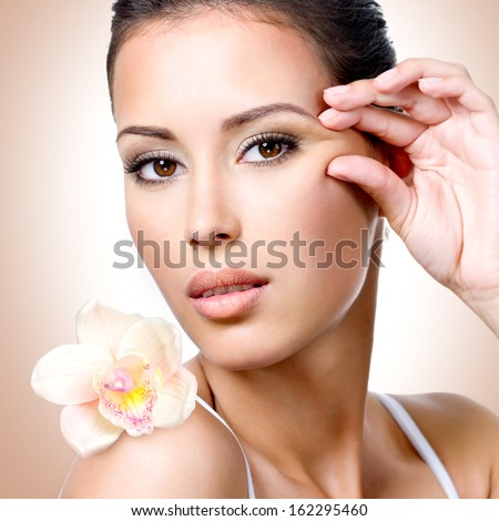 Face of beautiful woman with health skin and  flower over art background - stock photo