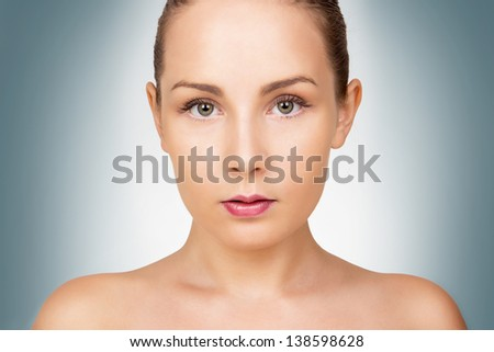 Face of beautiful young woman with perfect clean, healthy skin and bare shoulders - stock photo