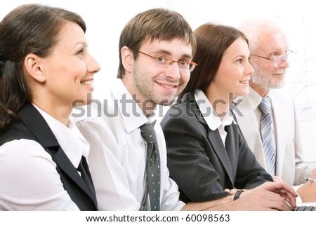 Face of businessman looking at camera with smile between his colleagues - stock photo