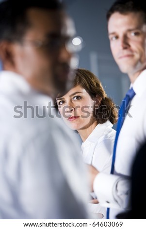 Face of businesswoman, 40s, looking out between two men standing beside