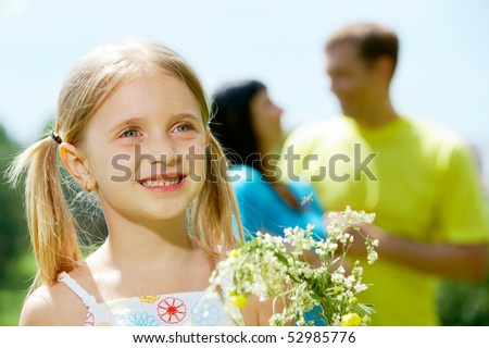 Face of cheerful girl looking aside with smile on background of her father and mother - stock photo