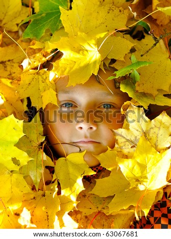 Face of child in leaves in autumn - stock photo