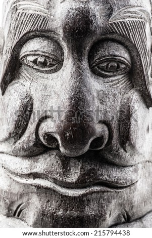 Face of dark wooden tribal idol in woods with a enigmatic expression - stock photo