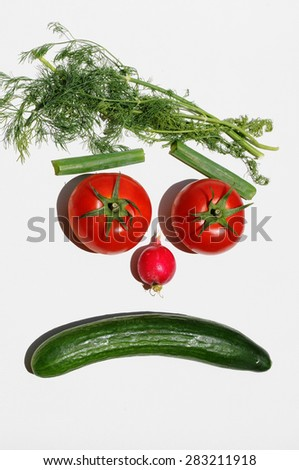 Face of disappointment made of vegetables - tomatoes, cucumber, radish and dill herbs on white background. Top view - stock photo