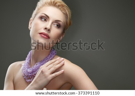 Face of elegance. Studio shot of a gorgeous mature woman wearing necklace posing on grey background - stock photo