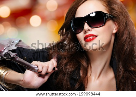 Face of fashion luxury woman in black trendy sunglasses with handbag