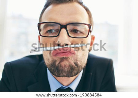 Face of funny businessman in eyeglasses holding pen between nose and lips - stock photo