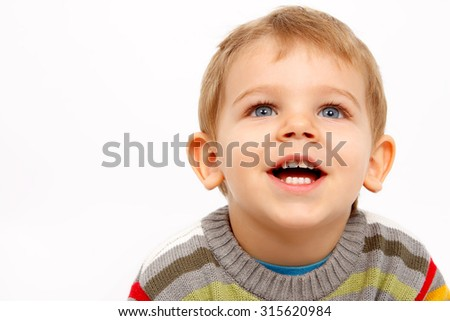 Face of happy kid in winter clothes looking up - stock photo