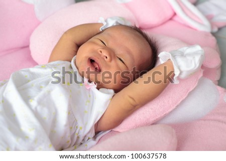 face of infant sleep on the bed and smiling - stock photo