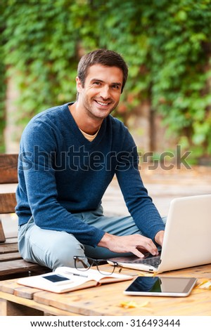 Face of job satisfaction. Smiling young man working on laptop and looking at camera while sitting at the wooden table outdoors - stock photo