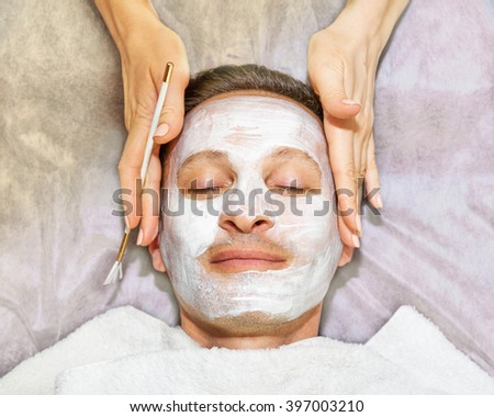Face of laying man with cream mask, hands of beautician with brush, beauty, spa - stock photo