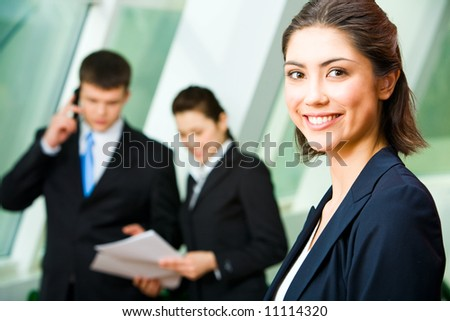 Face of pretty professional with charming smile on the background of colleagues - stock photo