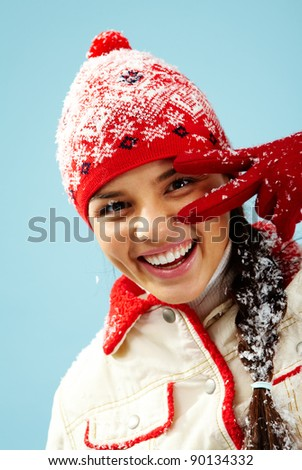 Face of pretty woman in gloves and knitted winter cap looking at camera with two fingers by her eye