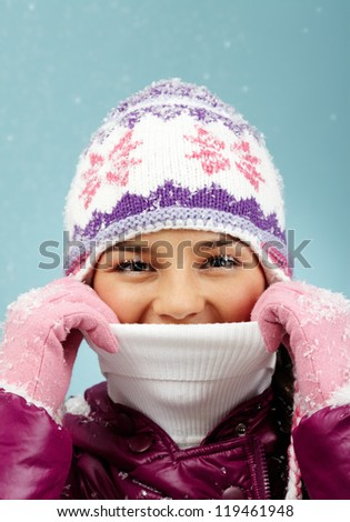 Face of pretty woman in knitted winter cap and gloves looking at camera