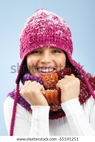 Face of pretty woman in knitted winter cap and scarf looking at camera with smile - stock photo
