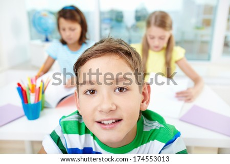 Face of smart lad looking at camera with two classmates on background
