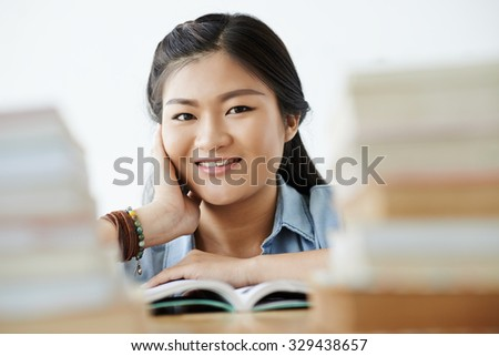 Face of smiling teenage girl reading book in a library