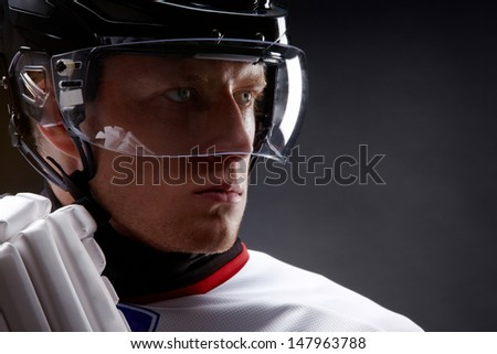 Face of sportsman in protective helmet over black background - stock photo