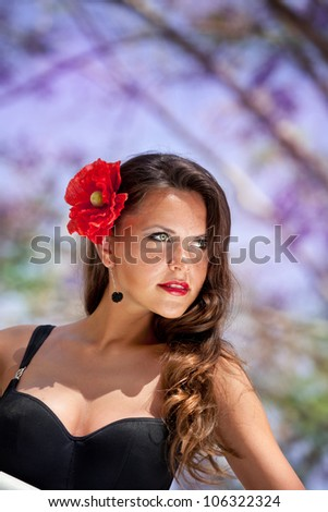 face of the nice girl with a hairpin in the form of a flower - stock photo