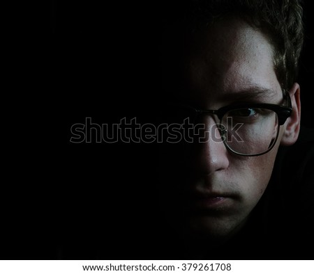 Face of the young man in glasses in low key - stock photo