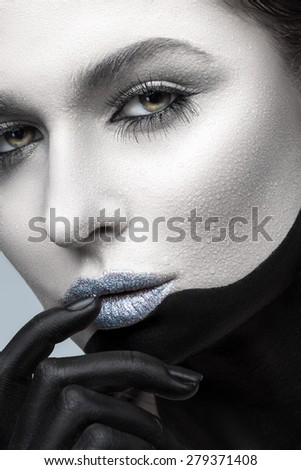Face of woman with water drops on black and white makeup closeup